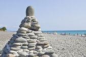 The pyramid of stones on sea coast. — Stock Photo