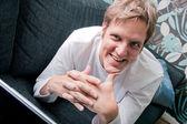 Homme souriant travaillant sur ordinateur portable sur le canapé — Photo