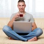 killen med laptop och te — Stockfoto