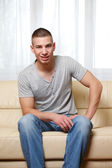 Young handsome man sitting on the sofa — Stock Photo