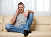 Young handsome man making a call at home — Stock Photo