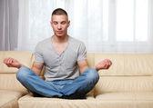 Handsome man making yoga on the sofa — Stock Photo