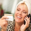 Smiling Robed Woman on Cell Phone With Credit Card — Stock Photo