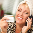 Smiling Robed Woman on Cell Phone With Credit Card - Stock Photo