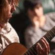 Young Musician Plays His Acoustic Guitar as Friend Listens - Stock Photo