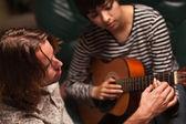 Giovane musicista insegna studentessa a suonare la chitarra — Foto Stock