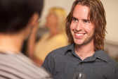 Smiling Young Man with Glass of Wine Socializing — Stock Photo