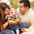 Royalty-Free Stock Photo: Happy Mixed Race Parents Playing with Their Son