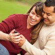 Attractive Mixed Race Couple Enjoying Their Camera Phone — Stock Photo