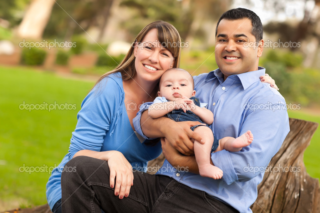 Happy Mixed Race Family Posing for A Portrait in the Park.  Stock Photo #4116605