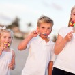 Cute Brother and Sisters Enjoying Their Lollipops Outside — Stock Photo