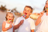 Cute Brother and Sisters Enjoying Their Lollipops Outside — Foto de Stock