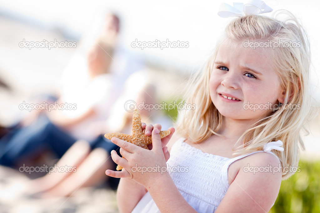 Adorable Little Blonde Girl with Starfish at The Beach.  Stock Photo #4231381