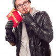 Warmly Dressed Young Man Holding Wrapped Gift To His Ear — Stock Photo