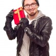 Warmly Dressed Young Man Holding Wrapped Gift To His Ear — Stock Photo #4323556