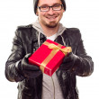 Warmly Dressed Young MHanding Wrapped Gift Out — Stock Photo #4323561
