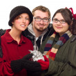 Three Friends Holding A Holiday Gift Isolated — Stock Photo