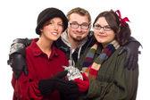 Drei freunde halten ein weihnachtsgeschenk, isoliert — Stockfoto
