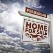 Royalty-Free Stock Photo: White Foreclosure Home For Sale Real Estate Sign Over Clouds and