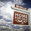 Red Sold Home For Sale Real Estate Sign Over Clouds and Sky — Stock Photo #4676558