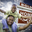 Royalty-Free Stock Photo: African American Father with Son In Front of Sold Home For Sale