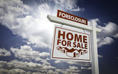 White Foreclosure Home For Sale Real Estate Sign Over Clouds and — Stock Photo
