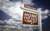 Red Foreclosure Home For Sale Real Estate Sign Over Clouds and S — Stock Photo