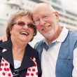 Senior Couple On Shore in Front of Cruise Ship - Stock Photo