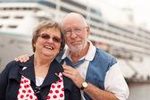 Casal sênior na praia na frente do navio de cruzeiro — Foto Stock