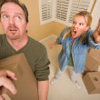 Stressed Man Moving Boxes for Demanding Wife - Stock Photo