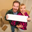 Happy Couple Holding Blank Sign in Room with Packed Boxes — Stock Photo