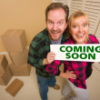 Goofy Couple Holding Coming Soon Sign in Room with Boxes - Stock Photo