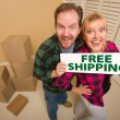 Goofy Couple Holding Free Shipping Sign Surrounded by Boxes - Stock Photo
