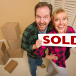 Goofy Couple Holding Sold Sign Surrounded by Boxes — Stock Photo