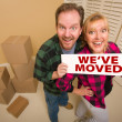 Goofy Couple Holding We've Moved Sign Surrounded by Boxes — Stock Photo