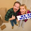 Goofy Couple Holding We're Moving Sign Surrounded by Boxes — Stock Photo