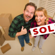 Stock Photo: Goofy Couple Holding Sold Sign Surrounded by Boxes
