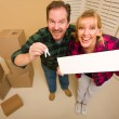 Goofy Couple Holding Keys and Blank Sign Surrounded by Boxes — Stock Photo #4783072