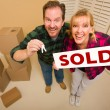 Goofy Couple Holding Key and Sold Sign Surrounded by Boxes — Stock Photo #4783074