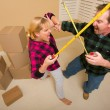 Couple Having Fun Sword Fight with Tape Measures - Stock Photo