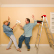 Fun Couple Playing Sword Fight with Paint Rollers — Stock Photo