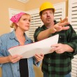 contractor in hardhat discussing plans with woman — Stock Photo