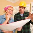 Contractor in Hardhat Discussing Plans with Woman - Stock Photo