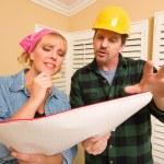 Auftragnehmer in Bauarbeiterhelm Pläne mit Frau besprechen — Stockfoto
