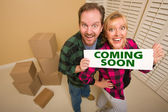 Goofy Couple Holding Coming Soon Sign in Room with Boxes — Stock Photo