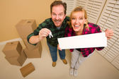 Goofy Couple Holding Keys and Blank Sign Surrounded by Boxes — Stock Photo