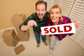 Goofy Couple Holding Key and Sold Sign Surrounded by Boxes — Stock Photo