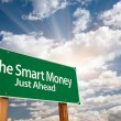 The Smart Money Green Road Sign and Clouds - Stock Photo