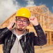 Royalty-Free Stock Photo: Young Construction Worker on Cell Phone In Front of House