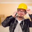 Royalty-Free Stock Photo: Young Contractor Wearing Hard Hat on Cell Phone In House